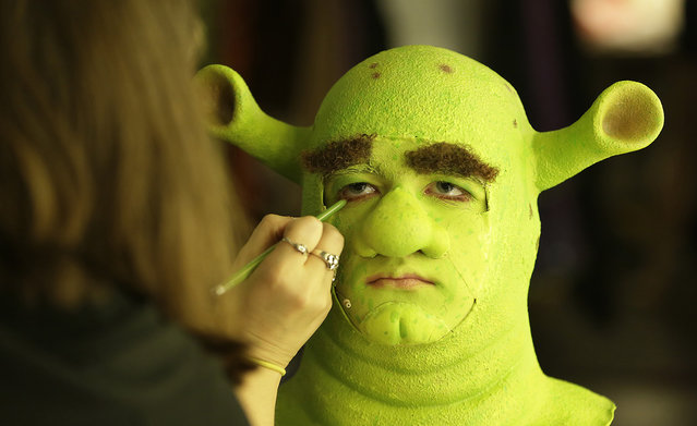 Theater department manager and assistant makeup designer Audrey Siegler applies eyebrows to Christian Meany before the dress rehearsal of Shrek the Musical on Wednesday, July 15, 2015, at the Patel Conservatory in Tampa, Fla. The performance is part of Patel's summer production camps. (Photo by James Borchuck/The Tampa Bay Times via AP Photo)