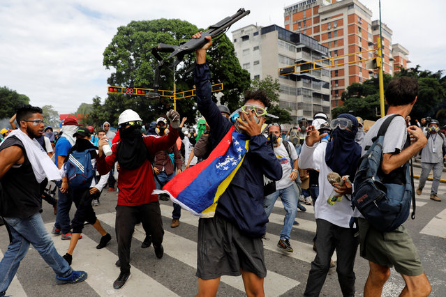 Opposition supporters show a shotgun that they snatched from riot police during a rally against President Nicolas Maduro in Caracas, Venezuela on May 3, 2017. (Photo by Carlos Garcia Rawlins/Reuters)