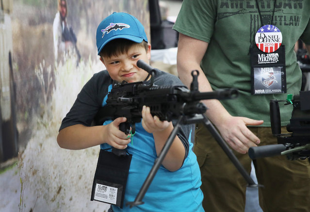 Christian Florea, 10,  looks over an FN MK 48 machine gun at the NRA Annual Meetings & Exhibits on May 21, 2016 in Louisville, Kentucky. (Photo by Scott Olson/Getty Images)