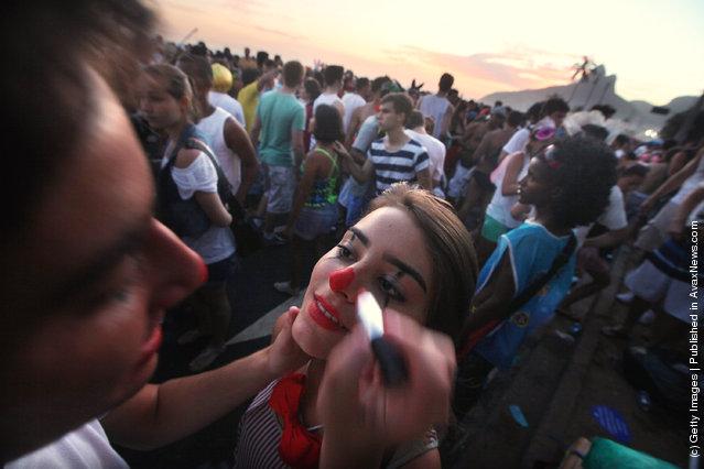 A man paints a woman's face during Carnival celebrations along Ipanema beach in Rio de Janiero, Brazil