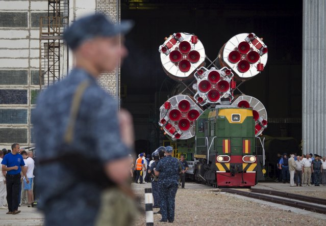 Policemen stan guard as the Soyuz TMA-17M spacecraft is transported from an assembling hangar to its launch pad at the Baikonur cosmodrome, Kazakhstan, July 20, 2015. (Photo by Shamil Zhumatov/Reuters)