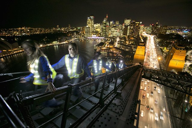 Participants wear illuminated vests as they climb the Sydney Harbour Bridge high above the city traffic during a preview of the Vivid Sydney light and music festival, on May 20, 2014. Beginning Friday, Sydney will light up at night as part of the festival, combining outdoor lighting sculptures and installations at one of the world's largest creative industry forums. (Photo by Jason Reed/Reuters)