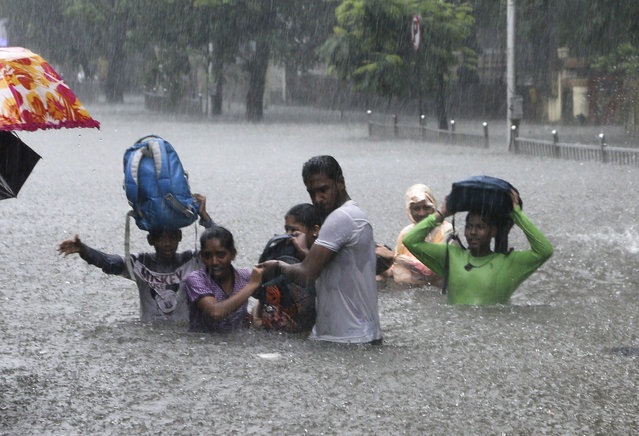 In this September 4, 2019, file photo, people hold hands and navigate their way through a flooded street as it rains in Mumbai, India. The number of people threatened by climate change-triggered flooding is about three times higher than previously thought, a new study says. But it's not because of more water. It's because the land, especially in Asia and the developing world, is several feet lower than what space-based radar has calculated, according to a study in the journal Nature Communications Tuesday, Oct. 29. (Photo by Rajanish Kakade/AP Photo/File)