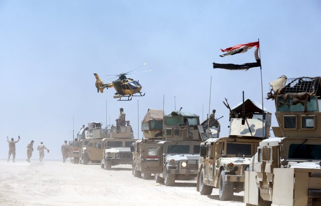 An Iraqi helicopter flies over military vehicles in Husaybah, in Anbar province July 22, 2015. (Photo by Reuters/Stringer)