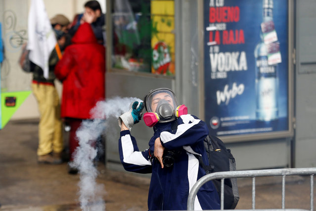 A demonstrator throws a tear gas canister during an unauthorized march called by secondary students to protest against government education reforms in Santiago, Chile, May 26, 2016. (Photo by Ivan Alvarado/Reuters)