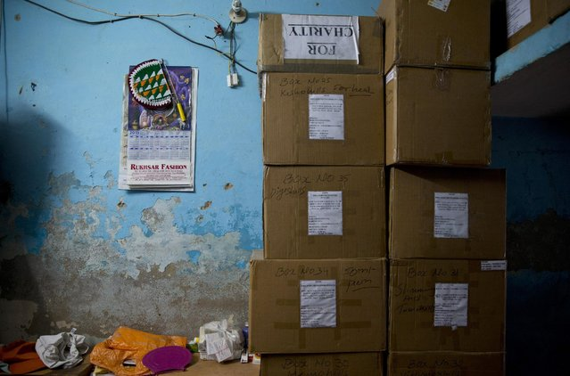 In this June 8, 2015 photo, a part of the tiny living space of Omkarnath, who has also rented a separate small room to store medicines, is occupied by boxes of medicines at a fetid slum in New Delhi, India. (Photo by Saurabh Das/AP Photo)
