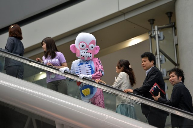 An employee (C) of Japan's toy maker Megahouse (C) rides an escalator after the opening ceremony of the annual Tokyo Toy Show in Tokyo on June 12, 2014. Some 160,000 poeple are expecting to visit Asia's largest four-day toy trade show. (Photo by Yoshikazu Tsuno/AFP Photo)