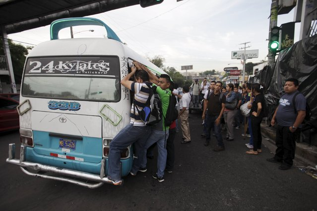 People run to ride in a microbus during the second day of a suspension of public transport services in Mejicanos, El Salvador July 28, 2015. (Photo by Jose Cabezas/Reuters)