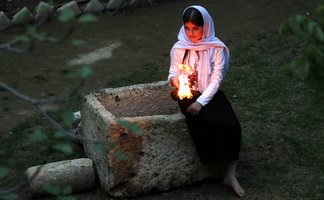 Iraqi Yazidis light candles and paraffin torches outside Lalish temple situated in a valley near Dohuk, 430 km (260 miles) northwest of Baghdad, during a ceremony to celebrate the Yazidi New Year on April 18, 2017. The Yazidis, who number about 1.6 million, commemorate the arrival of the light into the world during the celebration. (Photo by Safin Hamed/AFP Photo)