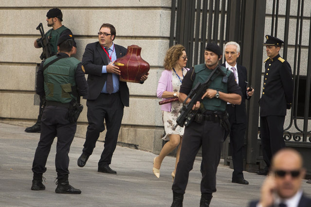 The king's crown is being carried under tight security before Spain's newly crowned King Felipe VI arrives at the Parliament in Madrid, Spain, Thursday, June 19, 2014. Felipe is being formally proclaimed monarch Thursday after 76-year-old King Juan Carlos abdicated. Felipe was to swear an oath at a ceremony with lawmakers in Parliament in front of Spain's 18th-century crown and 17th-century scepter. (Photo by Andres Kudacki/AP Photo)