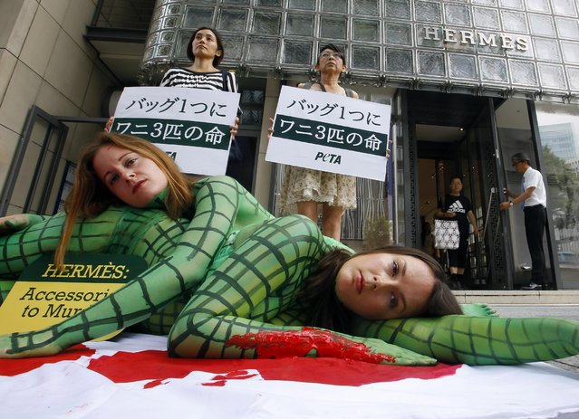 "Activists of People for the Ethical Treatment of Animals, or PETA perform with their bodies painted to look like slaughtered crocodiles in front of a Hermes shop at Tokyo's Ginza shopping district, Thursday, July 30, 2015. The banners read ""It takes three crocodiles to make one handbag"". (Photo by Shizuo Kambayashi/AP Photo)"
