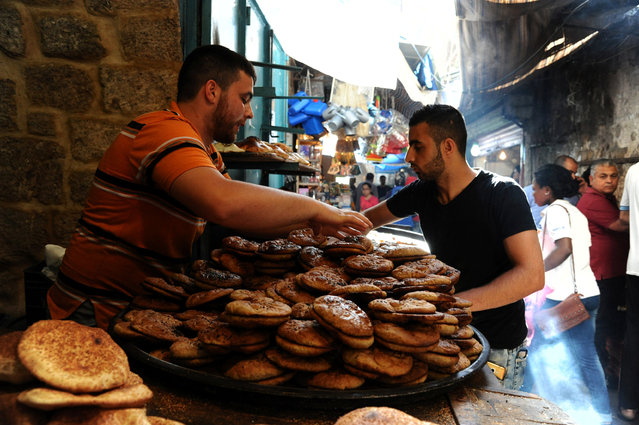 A man arranges sweet bread on the first day of the holy fasting month of Ramadan in Tripoli, Lebanon June 6, 2016. (Photo by Omar Ibrahim/Reuters)