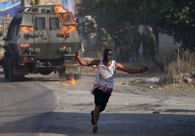 A Palestinian protester runs after throwing a molotov cocktail towards Israeli soldiers during clashes following the funeral of Palestinian youth Laith al-Khaldi, in Jalazoun refugee camp near the West Bank city of Ramallah August 1, 2015. (Photo by Mohamad Torokman/Reuters)