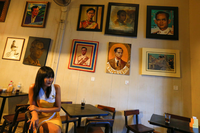 A hostess sits at a restaurant with paintings depicting Thailand's King Bhumibol Adulyadej hanging on a wall in Bangkok, Thailand, June 6, 2016. (Photo by Athit Perawongmetha/Reuters)