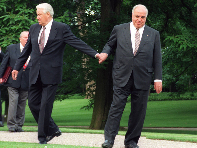 The June 8, 1998 file photo shows German Chancellor Helmut Kohl, right, guiding Russian President Boris Yeltsin through the park after Yeltsin's arrival for talks at the Bonn Chancellery. (Photo by Fritz Reiss/AP Photo)