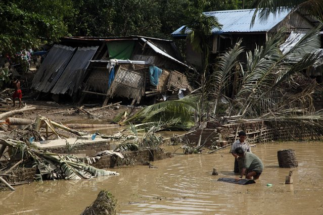 Local residents work in water near their damaged residence by flood in Myauk U, Rakhine State, western Myanmar, Tuesday, August 4, 2015. (Photo by Khin Maung Win/AP Photo)