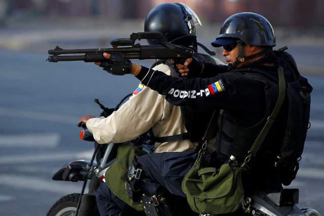 A riot security force member aims his weapon toward demonstrators during a rally against Venezuela's President Nicolas Maduro's government in Caracas, Venezuela, June 26, 2017. (Photo by Christian Veron/Reuters)