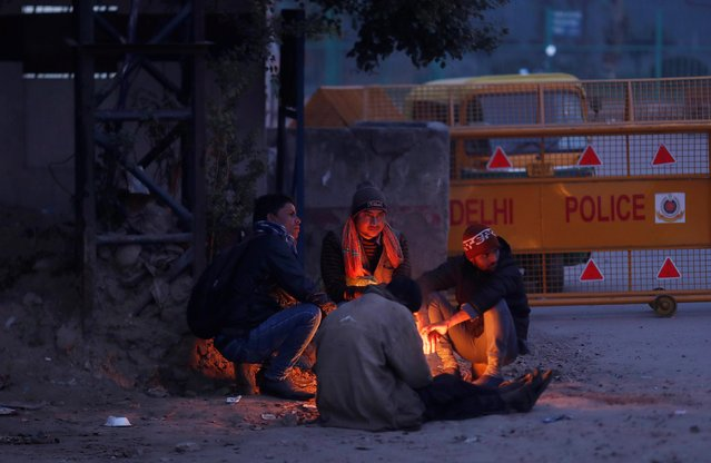 Men sit next to a bonfire on a road side during a cold winter evening in New Delhi, December 28, 2019. (Photo by Adnan Abidi/Reuters)