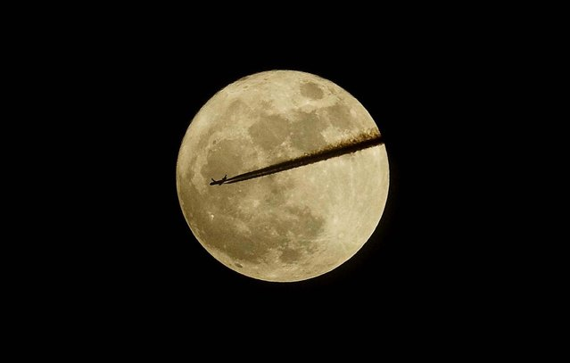 A plane flies past the moon as seen from Somerset in southern England