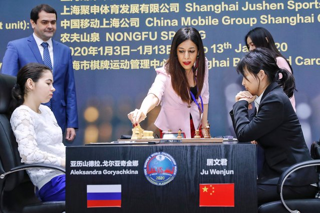 Shohreh Bayat (C), chief arbiter for the match between Aleksandra Goryachkina (front L) of Russia and Ju Wenjun (front R) of China, prepares for the match during the 2020 International Chess Federation (FIDE) Women's World Chess Championship in Shanghai on January 11, 2020. (Photo by AFP Photo/China Stringer Network)