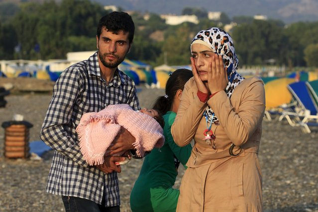 Syrian refugee Mohamed from Idlib holds his 2-month-old daughter Malak next to his wife Kawsr moments after arriving on a beach on the Greek island of Kos, after crossing a part of the Aegean sea from Turkey on a overcrowded dinghy, August 9, 2015. (Photo by Yannis Behrakis/Reuters)