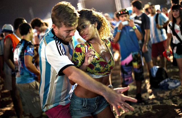 A woman from Brazil and a man from Argentina dance samba at the World Cup Fan Fest 2014, on Copacabana beach, in Rio de Janeiro, Brazil, Wednesday, July 9, 2014. The flood of foreign football fans, the vast majority of them men, has been a boon for the single ladies of Brazil, where a demographic imbalance means women outnumber men by more than 4 million nationally. (Photo by Silvia Izquierdo/AP Photo)