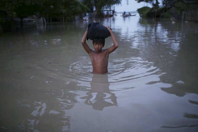In this August 3, 2015, photo, a boy makes his way through floodwaters in Minbu, Magway division, in Myanmar. (Photo by Hkun Lat/AP Photo)