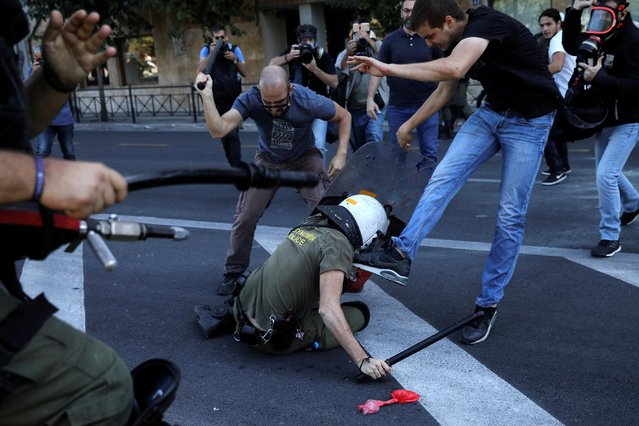 Protesters from the Communist-affiliated trade union PAME attack a riot police officer as they clash during a demonstration against the visit of U.S. Secretary of State Mike Pompeo in Athens, Greece, October 5, 2019. (Photo by Alkis Konstantinidis/Reuters)