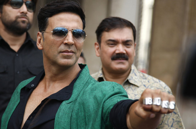"In this Friday, October 11, 2013 file photo, Bollywood actor Akshay Kumar shows his rings during a promotional event during a promotional event of his movie ""Boss"" in Hyderabad, India. Bollywood films, with their colorful sets and hyper-coordinated song-and-dance numbers, have catapulted five Indians into the ranks of world's highest paid male actors. Three of those actors – Salman Khan, Amitabh Bachchan and Akshay Kumar – were in the top 10, outranking Hollywood A-listers such as Dwayne ""The Rock"" Johnson and Leonardo DiCaprio. (Photo by Mahesh Kumar A./AP Photo)"