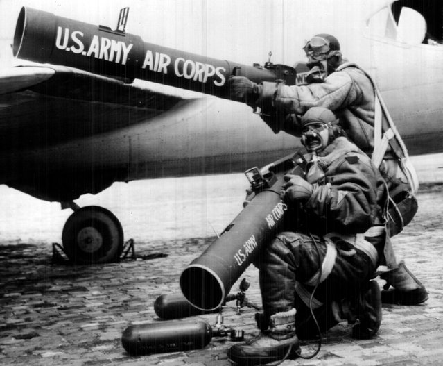 "Major George W. Goddard (standing), chief of the army air corps photographic branch at Wright field, Dayton, O., and Sgt. A. E. Mathos (kneeling), army aerial photographer, are shown here ""warming up"" The huge aerial cameras they will use  in ""shooting"" the ring eclipse of the sun in 1940. They are wearing the equipment they will use when a huge army bomber takes them up more than five miles. Maj. Goddard has a 60-inch telephoto camera, Sgt. Mathos a 40-inch camera. (Photo by Denver Post/Library archive)"