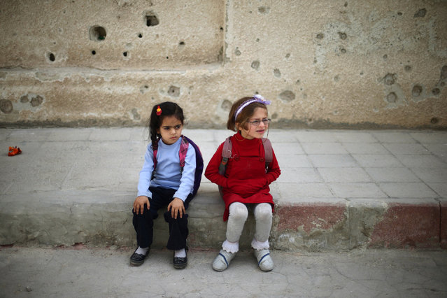 Girls sit next to a riddled wall in a school yard in the town of Douma, eastern Ghouta in Damascus, Syria May 24, 2016. (Photo by Bassam Khabieh/Reuters)
