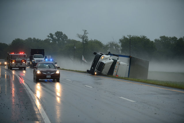 A tractor trailer truck lies on its side in the median of U.S. Route 13 in Cheriton, Va. while a fire engine responds to a nearby campground after a severe storm passed through the area, Thursday, July 24, 2014. (Photo by Jay Diem/AP Photo/Eastern Shore News)