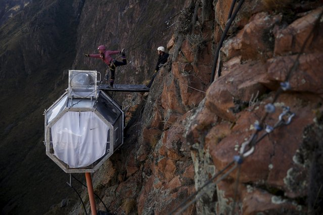 A guest does yoga above a sleeping pod at the Skylodge Adventure Suites in the Sacred Valley in Cuzco, Peru, August 14, 2015. (Photo by Pilar Olivares/Reuters)