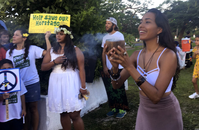 Eva Aguon Cruz, 30, holds a cup with burnt flower as a ritual to call for protections from the spirits as about a hundred people gathered at Chief Kepuha Park in Hagatna, Guam for a rally for peace Monday, August 14, 2017. Residents of Guam held a demonstration on Monday in support of peace.  The U.S. territory has been the subject of threats from North Korea in its escalating war of words with the U.S. President Donald Trump's administration. (Photo by Tassanee Vejpongsa/AP Photo)