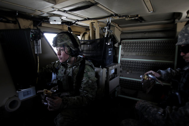 "U.S. female soldier SPC Erica Taliaferro from 549th MP Company, Task Force Bronco eats MRE sandwich with an ISAF Afghan police trainer (R) inside an armored vehicle as troops stayed inside their vehicles for 15 hours during a two-day joint U.S-Afghan military mission conducting ""Route Clearing Patrol"", finding and removing roadside bombs on roads, in Nangarhar province, eastern Afghanistan March 8, 2012. (Photo by Erik De Castro/Reuters)"