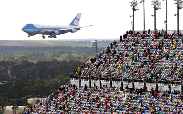 Race fans watch from the grandstands as Air Force One circles the Daytona International Speedway as President Donald Trump makes his arrival to attend the NASCAR Daytona 500 auto race at Daytona International Speedway, Sunday, February 16, 2020, in Daytona Beach, Fla. (Photo by Jim Topper/AP Photo)