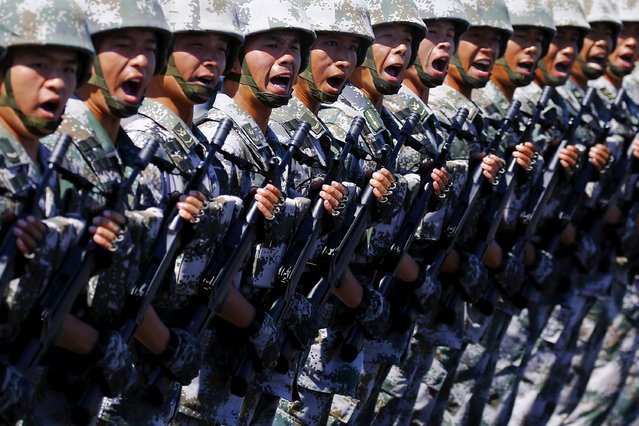 Soldiers of China's People's Liberation Army shout as they march with their weapons during a training session for a military parade to mark the 70th anniversary of the end of World War Two, at a military base in Beijing, China, August 22, 2015. (Photo by Damir Sagolj/Reuters)