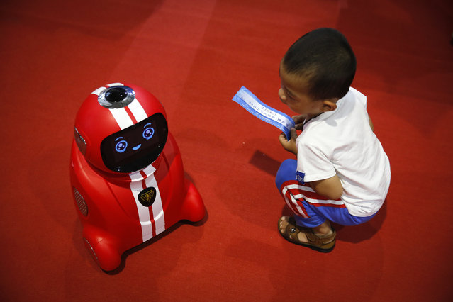 A child holding an entrance ticket watches a smart self-learning robot during the World Robot Conference at the Yichuang International Conference and Exhibition Centre in Beijing, Wednesday, August 23, 2017. The annual conference is a showcase of China's burgeoning robot industry ranging from companion robots to those deployed on manufacturing assembly line and entertainment. (Photo by Andy Wong/AP Photo)