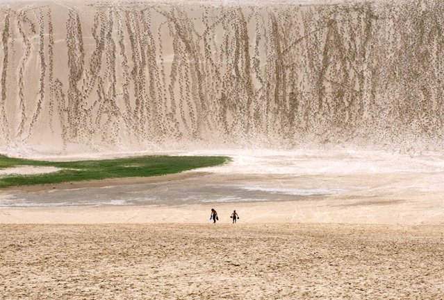 Two children walk on the Tottori sand dunes on July 21, 2012 in Tottori, Japan. The dunes are more than 11 square miles and have existed for more than 100,000 years but are shrinking in size due to a government reforestation program following World War II. (Photo by Buddhika Weerasinghe)