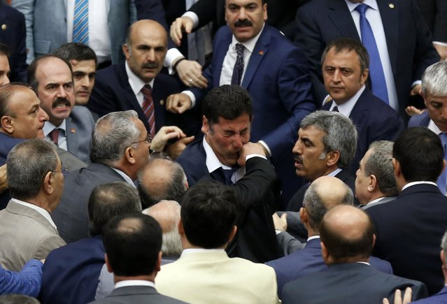 Muhyettin Aksak, a lawmaker from the ruling AK Party (AKP), punches Nationalist Movement Party's (MHP) Sinan Ogan (C) during a debate at the parliament in Ankara August 4, 2014. Three member of parliament were injured during a debate in the Turkish parliament turned into an all-out fist fight on Monday, private Dogan News Agency reported, and said the session was adjourned until Tuesday. (Photo by Reuters/Stringer)