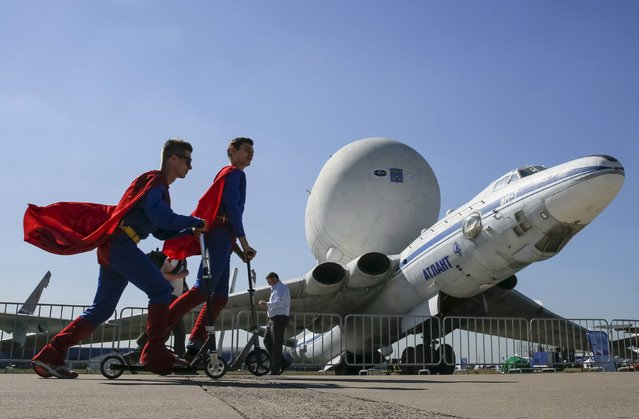 Promoters skate past a Myasishchev VM-T Atlant strategic airlift airplane on display at the MAKS International Aviation and Space Salon in Zhukovsky, outside Moscow, Russia, August 25, 2015. (Photo by Maxim Shemetov/Reuters)