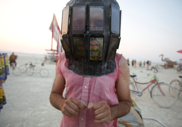 Derek Schoonmaker walks on the playa with his helmet made of android phones during the annual Burning Man festival in the Black Rock Desert of Nevada, U.S. on September 1, 2017. (Photo by Jim Urquhart/Reuters)