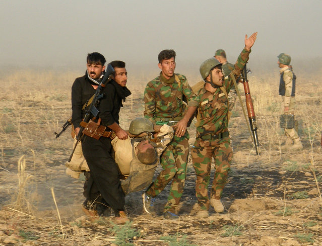 An injured Kurdish officer is taken for treatment, during a military operation to regain control of some villages from Islamic State group fighters south of oil-rich city of Kirkuk, 180 miles (290 kilometers) north of Baghdad, Iraq, Wednesday, August 26, 2015. (Photo by AP Photo)