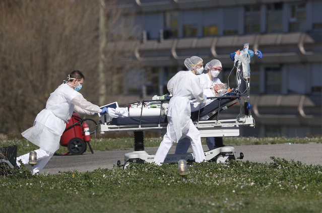 A victim of the Covid-19 virus is evacuated from the Mulhouse civil hospital, eastern France, Monday March 23, 2020. The Grand Est region is now the epicenter of the outbreak in France, which has buried the third most virus victims in Europe, after Italy and Spain. (Photo by Jean-Francois Badias/AP Photo)