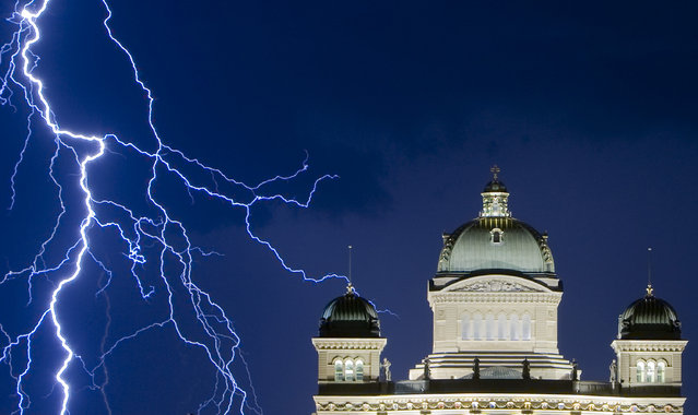 Lightning illuminates the sky during a thunderstorm over the Swiss Federal Palace in Bern July 17, 2009. (Photo by Michael Buholzer/Reuters)