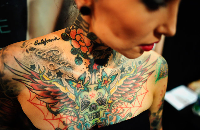 A visitor to a Tattoo and Piercing Convention event shows her tattoos in Dortmund, Germany, on June 15, 2012. (Photo by Sascha Schuermann/AP Photo)