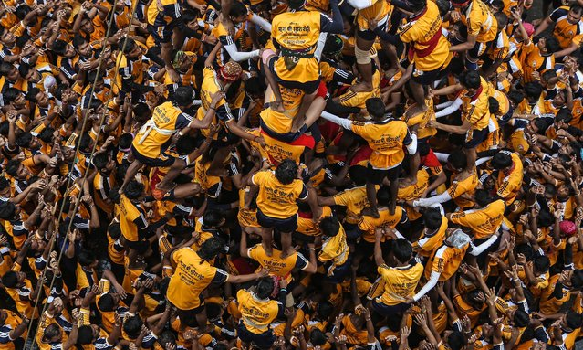 """Indian devotees form a human pyramid to reach and break a """"dahi-handi"""" (curd-pot), on occasion of the Janmashtami Festival in Mumbai, India, 18 August 2014. (Photo by Divyakant Solanki/EPA)"""