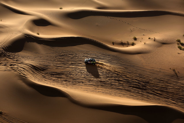 Mini team Yazeed Mohamed al-Rahji and copilot Timo Gottschalk compete in Inner Mongolia's Gobi desert, ending the 13th special stage of the Silkway rally on July 22, 2016. 130 competitors are racing over 10,734 kilometres crossing three countries and two continents from Moscow to Beijing. (Photo by Patrick Baz/AFP Photo)