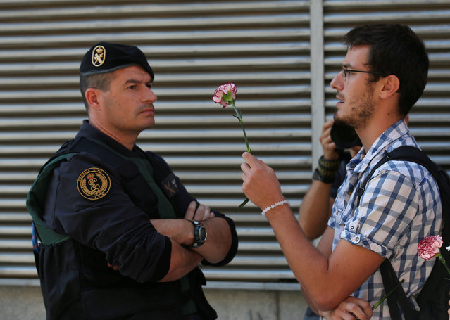 A man holds up a carnation next to a Spanish civil guard during a raid on a Unipost office in search of material for the proposed October 1 referendum, in Terrassa, Spain, September 19, 2017. (Photo by Albert Gea/Reuters)