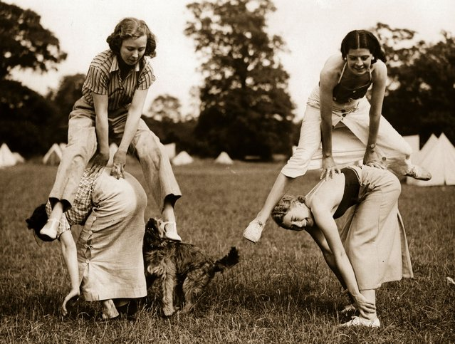 Four girl campers at Upshine, near Epping are pictured playing leap-frog with their dog trying to join in, 1936.